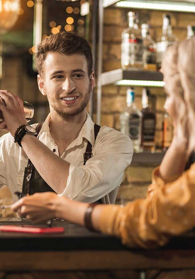 cute bartender shaking a drink talking to a blond girl